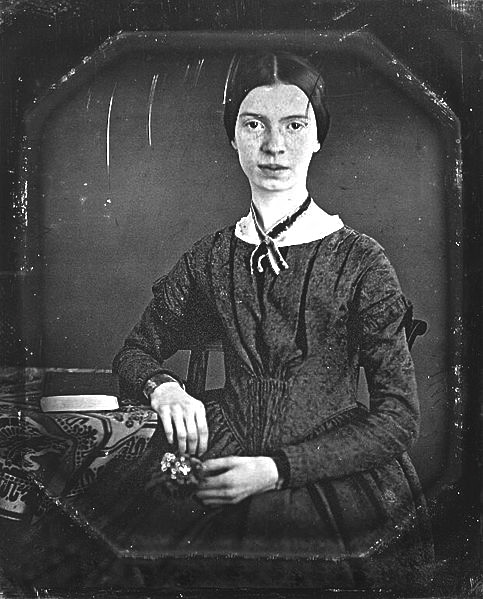 American poet Emily Dickinson sits with posies in a parlor